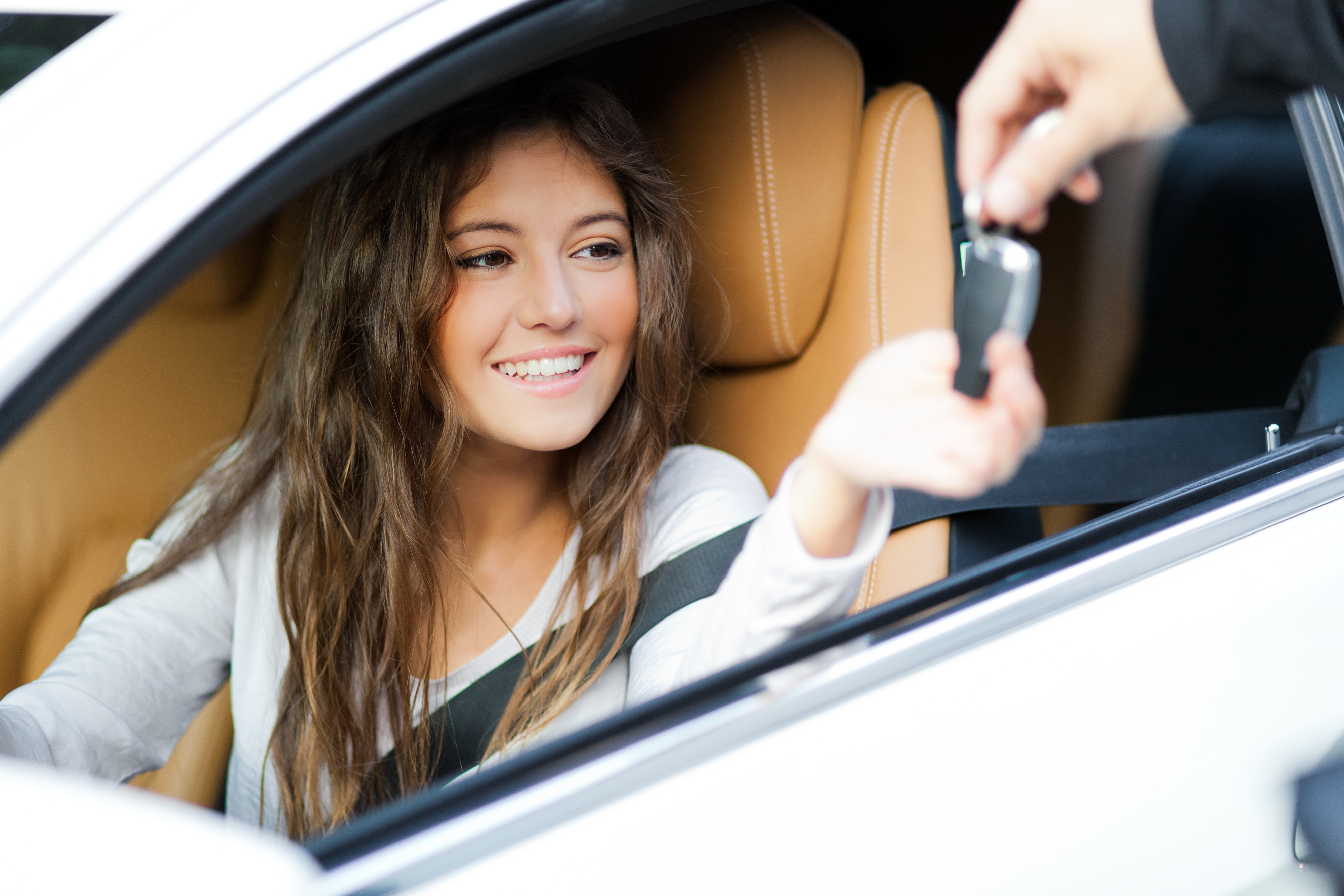 young woman in car receiving keys