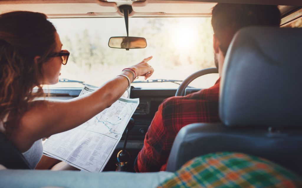 couple on road trip using map